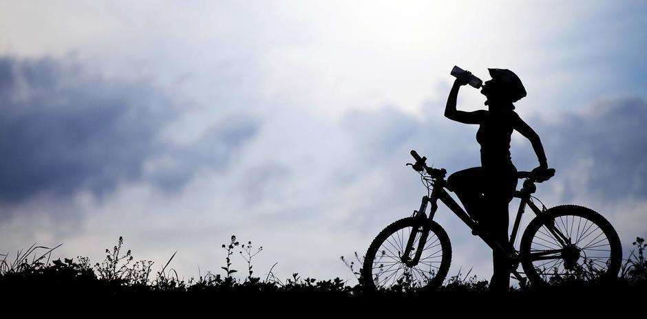 Ragazza in bicicletta che beve
